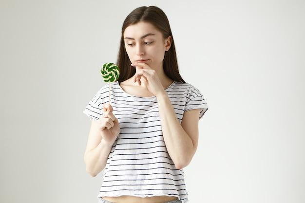 Doordachte jonge brunette vrouw in gestreepte top met harde snoep en kin aanraken met peinzende uitdrukking, denken, onzeker zijn over het hebben van ongezonde lolly