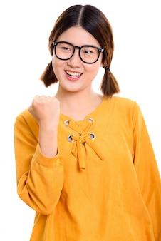 Doordachte jonge gelukkige aziatische vrouw die lacht terwijl u gemotiveerd kijkt