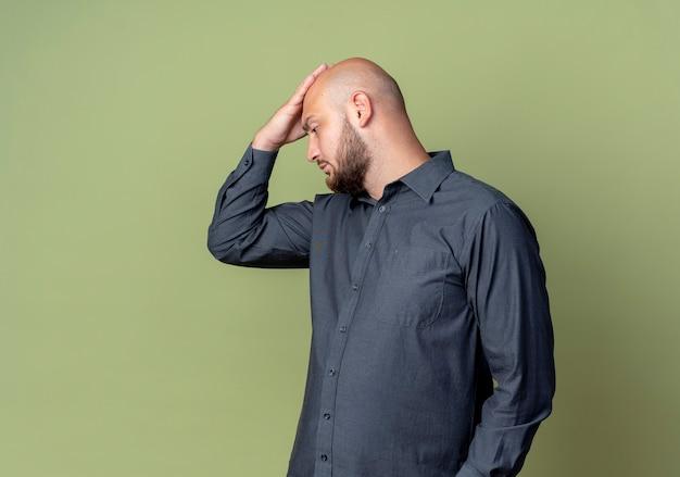 Doordachte jonge kale callcentermens die in profielmening hand op hoofd zet die neer geïsoleerd op olijfgroene muur kijkt