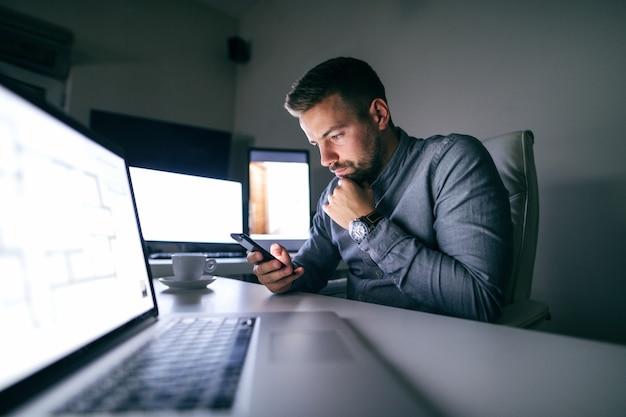 Doordachte jonge kaukasische bebaarde werknemer lezen of schrijven van bericht op slimme telefoon zittend in het kantoor 's avonds laat.