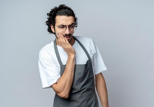 Doordachte jonge kaukasische mannelijke kapper bril en golvende haarband dragen uniform hand zetten gezicht kijken kant geïsoleerd op een witte achtergrond met kopie ruimte