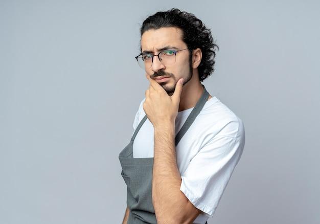 Doordachte jonge kaukasische mannelijke kapper bril en golvende haarband dragen uniform staande in profiel te bekijken kin geïsoleerd op een witte achtergrond met kopie ruimte aan te raken
