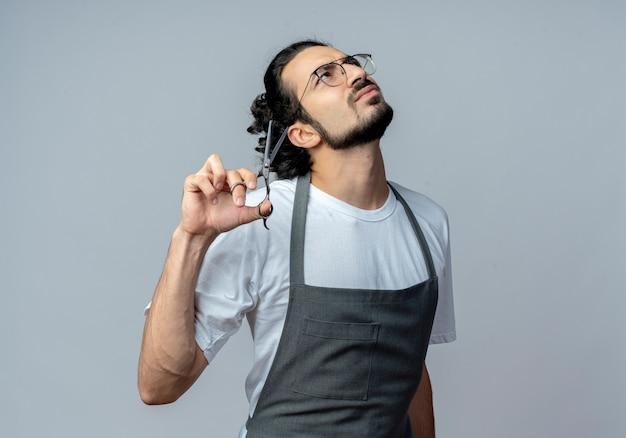 Doordachte jonge kaukasische mannelijke kapper bril en golvende haarband in uniform houden schaar opzoeken geïsoleerd op witte achtergrond met kopie ruimte