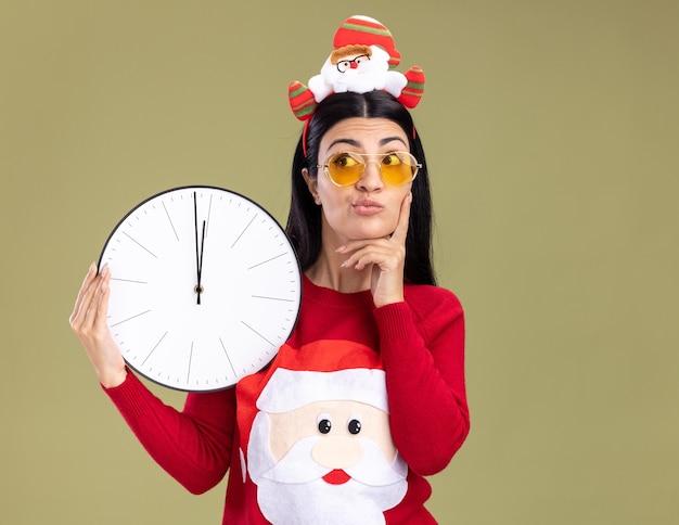 Doordachte jonge kaukasische meisje dragen hoofdband van de kerstman en trui met bril houden klok hand houden op kin kijken kant geïsoleerd op olijfgroene achtergrond met kopie ruimte