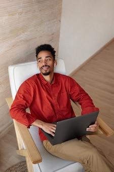 Doordachte jonge knappe bebaarde donkere man met kort kapsel laptop op zijn knieën houden en dromerig uit het raam kijken terwijl poseren op beige interieur