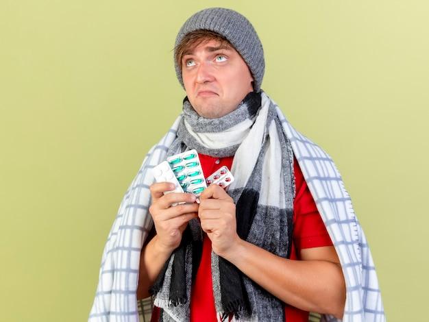 Doordachte jonge knappe blonde zieke man met winter muts en sjaal gewikkeld in een plaid bedrijf verpakkingen van medische pillen opzoeken geïsoleerd op olijfgroene muur