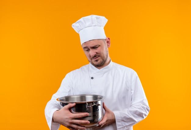 Doordachte jonge knappe kok in de ketel van de chef-kok de uniforme holding en bekijkt het op geïsoleerde oranje ruimte