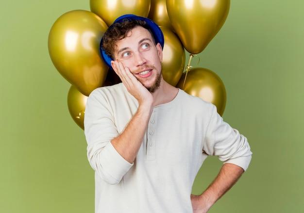 Doordachte jonge knappe slavische feestjongen die feestmuts draagt ?? die voor ballonnen staat die naar de zijkant kijkt en de handen op de taille en op het gezicht houdt geïsoleerd op olijfgroene muur