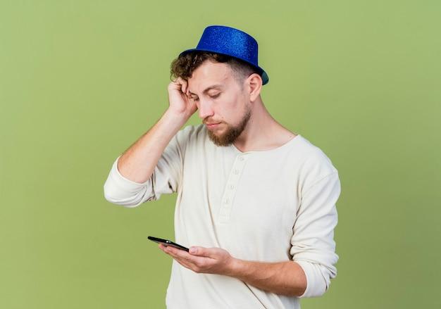 Doordachte jonge knappe slavische partij kerel dragen feestmuts houden en kijken naar mobiele telefoon aanraken hoofd geïsoleerd op olijfgroene achtergrond met kopie ruimte