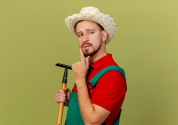 Doordachte jonge knappe slavische tuinman in uniform en hoed staande in profielweergave houden hark kijken kant aanraken kin geïsoleerd