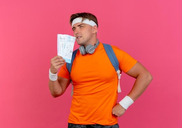 Doordachte jonge knappe sportieve man met hoofdband en polsbandjes en rugtas met koptelefoon op nek met vliegtuigkaartjes kijkend naar kant met hand op taille