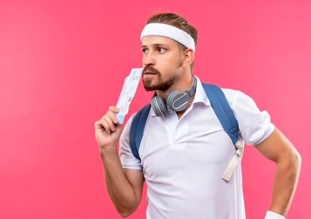 Doordachte jonge knappe sportieve man met hoofdband en polsbandjes en rugtas met koptelefoon op nek vliegtuigtickets te houden en kijken naar kant geïsoleerd op roze ruimte