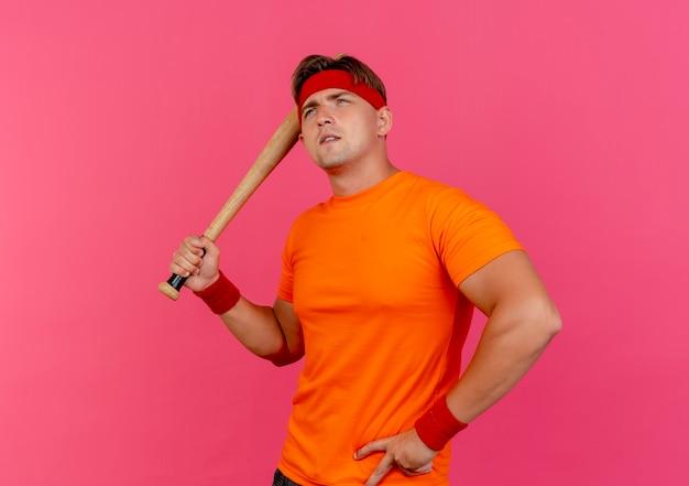 Doordachte jonge knappe sportieve man met hoofdband en polsbandjes met honkbalknuppel hand op taille en opzoeken geïsoleerd op roze muur