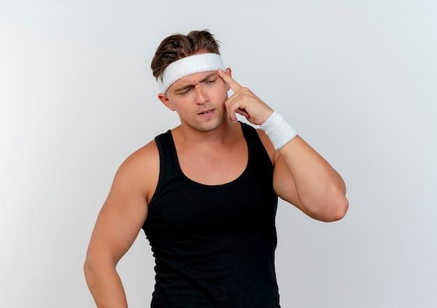Doordachte jonge knappe sportieve man met hoofdband en polsbandjes vinger op tempel zetten en neerkijkt geïsoleerd op een witte muur