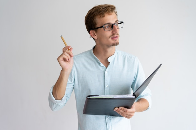 Doordachte jonge man die bestand, pen en met idee