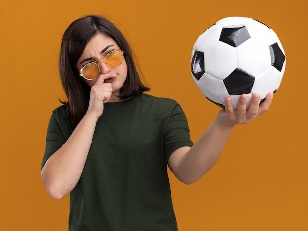 Doordachte jonge, mooie blanke meid met een zonnebril legt de hand op de kin die de bal vasthoudt en bekijkt