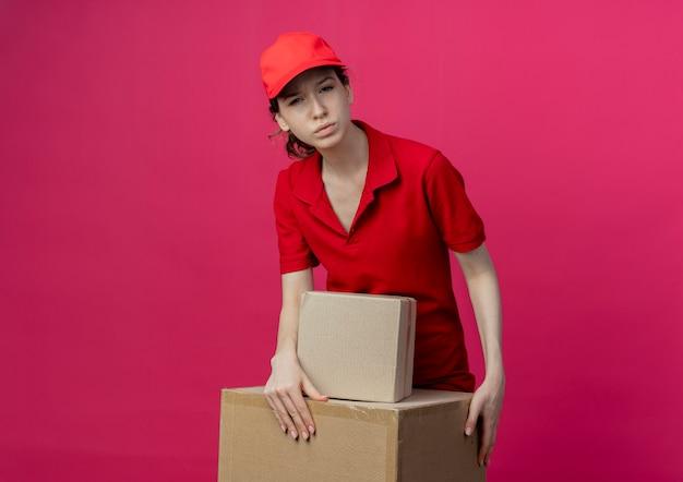 Doordachte jonge mooie levering meisje in rood uniform en pet handen zetten kartonnen doos geïsoleerd op karmozijnrode achtergrond met kopie ruimte
