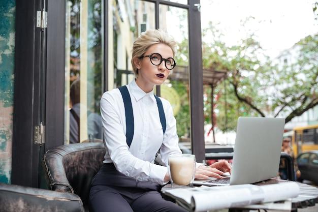 Doordachte jonge mooie vrouw die werkt met laptopcomputer in café binnenshuis