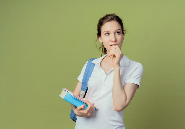 Doordachte jonge mooie vrouwelijke student die rugtas draagt die boek en notitieblok houdt die naar kant kijkt en hand dichtbij mond houdt die op olijfgroene achtergrond met exemplaarruimte wordt geïsoleerd