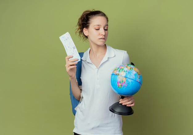 Doordachte jonge mooie vrouwelijke student draagtas achter houden en kijken naar globe lip bijten met vliegtuigtickets in een andere hand geïsoleerd op groene achtergrond met kopie ruimte