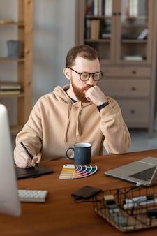 Doordachte jonge ontwerper in hoodie aan houten tafel zitten en kleurenpalet voor webdesign analyseren