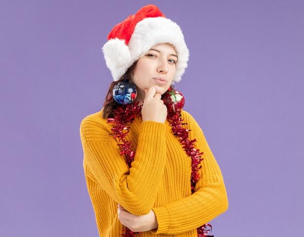 Doordachte jonge slavische meisje met kerstmuts en met slinger om nek legt hand op kin en houdt glazen bol ornamenten op oren geïsoleerd op paarse muur met kopie ruimte