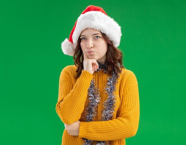 Doordachte jonge slavische meisje met kerstmuts en met slinger om nek legt vinger op gezicht en kijkt naar kant geïsoleerd op groene achtergrond met kopie ruimte