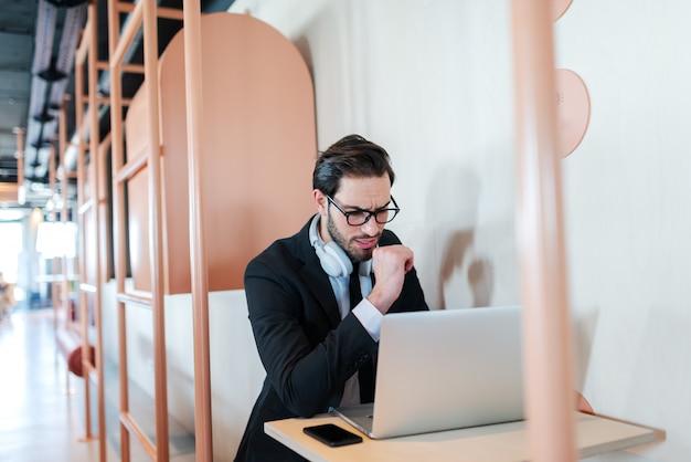 Doordachte jonge succesvolle advocaat gekleed in formele kleding met behulp van laptop zittend aan tafel.