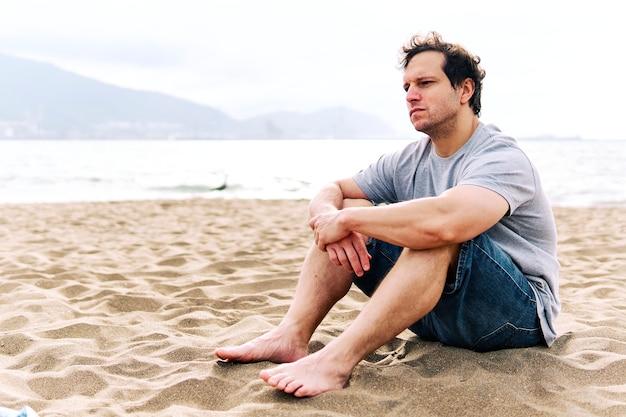 Doordachte jonge volwassen man zittend op het strandzand met melancholisch gebaar