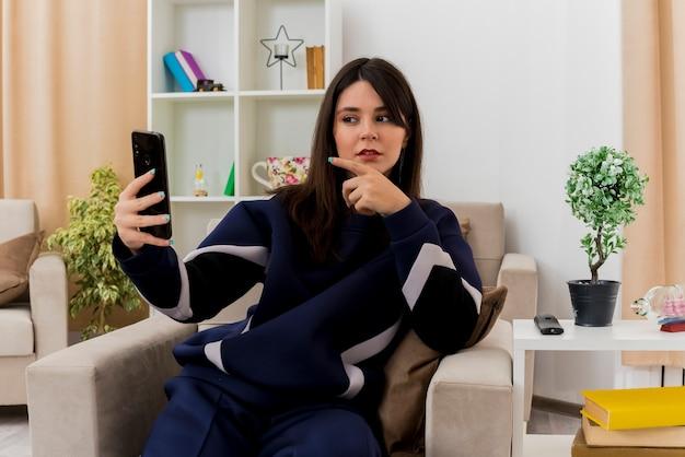 Doordachte jonge vrij kaukasische vrouw zittend op een fauteuil in ontworpen woonkamer houden en kijken naar mobiele telefoon en erop wijzen