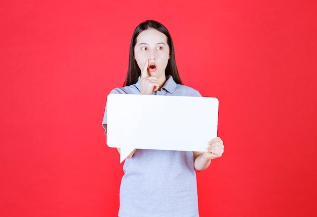 Doordachte jonge vrouw die een bord vasthoudt en wegkijkt