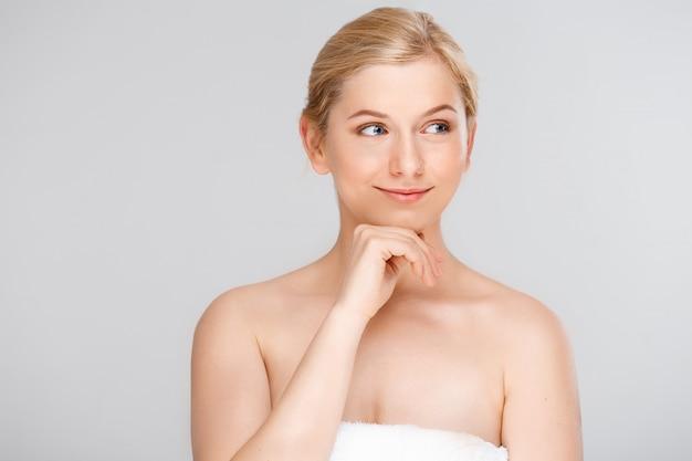 Doordachte jonge vrouw die lacht, bezoek spa salon