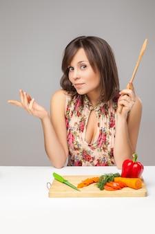 Doordachte jonge vrouw hakken groenten over de grijze achtergrond.