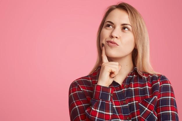 Doordachte jonge vrouw houdt wijsvinger bij kin, geconcentreerd, dagdroomt over iets