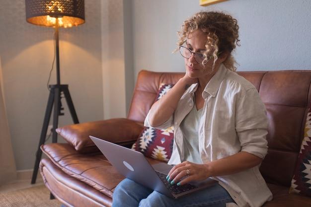 Doordachte jonge vrouw in brillen die computer gebruikt terwijl ze thuis op de bank zit