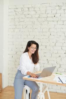 Doordachte jonge vrouw in slimme vrijetijdskleding die op kantoor werkt