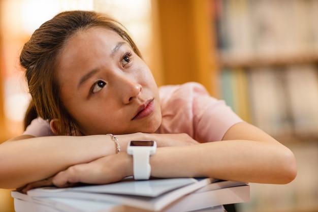 Doordachte jonge vrouw leunend op boek