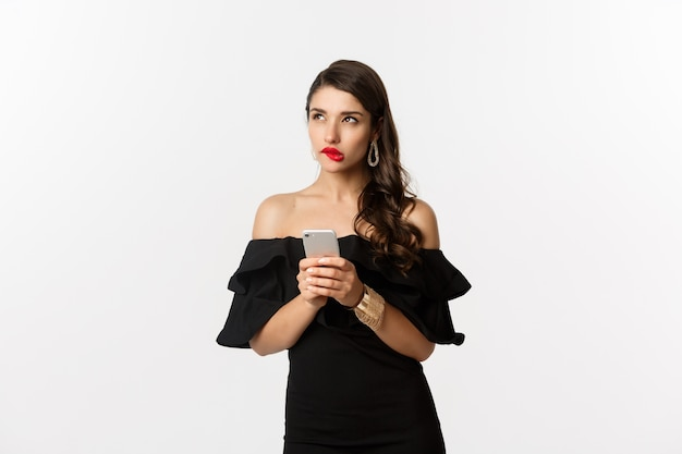 Doordachte jonge vrouw met behulp van smartphone en denken, opzoeken en nadenken, staande op witte achtergrond. kopieer ruimte