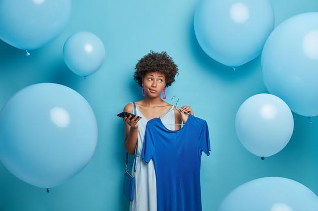 Doordachte jonge vrouw met donkere huid heeft krullend haar, elegante blauwe jurk op hanger, mobiele telefoon in de hand, jurken voor themafeest blauw, kijkt opzij, poseert tegen ballonnen met peinzende blik