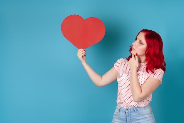 Doordachte jonge vrouw met rood haar houdt een hart van rood papier en raakt haar kin met haar hand