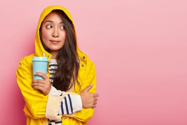 Doordachte jonge vrouw van gemengd ras voelt het koud, drinkt warme drank om zichzelf op te warmen, beeft na het lopen tijdens zware regenval