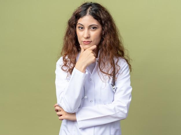Doordachte jonge vrouwelijke arts met een medisch gewaad en een stethoscoop die de hand op de kin houdt geïsoleerd op de olijfgroene muur met kopieerruimte