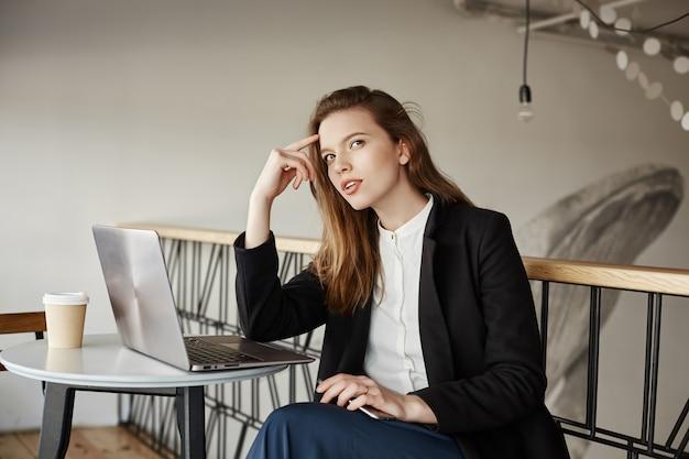 Doordachte jonge vrouwelijke freelancer werken in café met laptop, denken