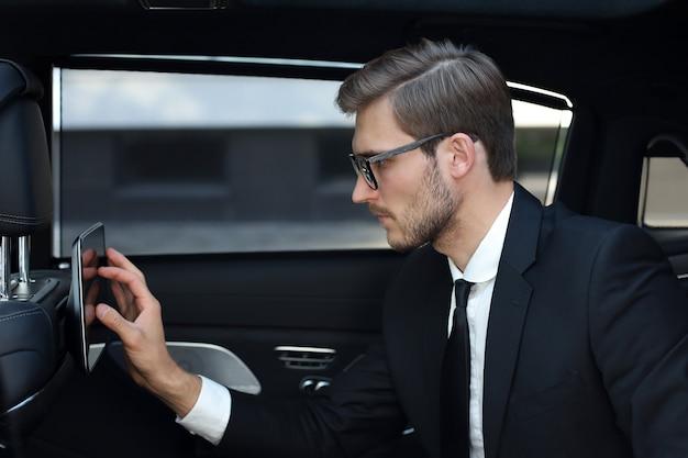 Doordachte jonge zakenman die in de luxe auto zit en zijn tablet gebruikt.
