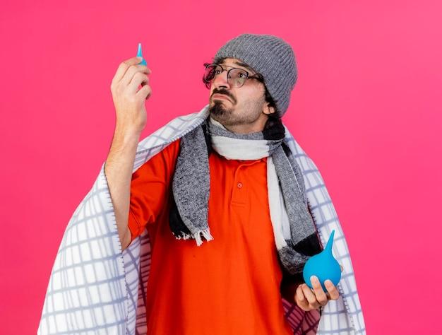 Doordachte jonge zieke man met bril, muts en sjaal gewikkeld in plaid bedrijf klysma's verhogen kleintje kijken ernaar geïsoleerd op roze muur