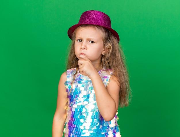 Doordachte kleine blonde meisje met paarse feestmuts legt de hand op de kin en kijkt geïsoleerd op de groene muur met kopie ruimte