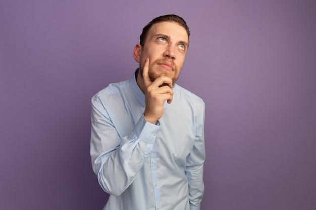 Doordachte knappe blonde man houdt kin en kijkt naar kant geïsoleerd op paarse muur