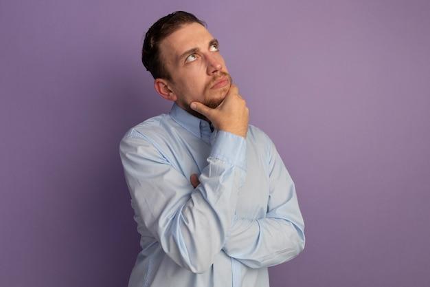 Doordachte knappe blonde man legt de hand op de kin en kijkt omhoog geïsoleerd op paarse muur