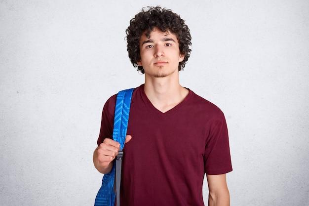 Doordachte knappe man met krullend zwart haar rechtop, met blauwe rugzak op zijn rug, gekleed in een donkerrood t-shirt