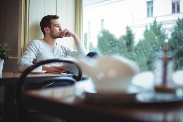 Doordachte man die door venster tijdens het lezen van de krant